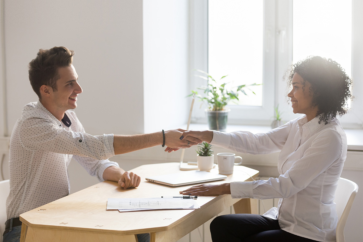 property manager and tenant shaking hands above a lease agreement
